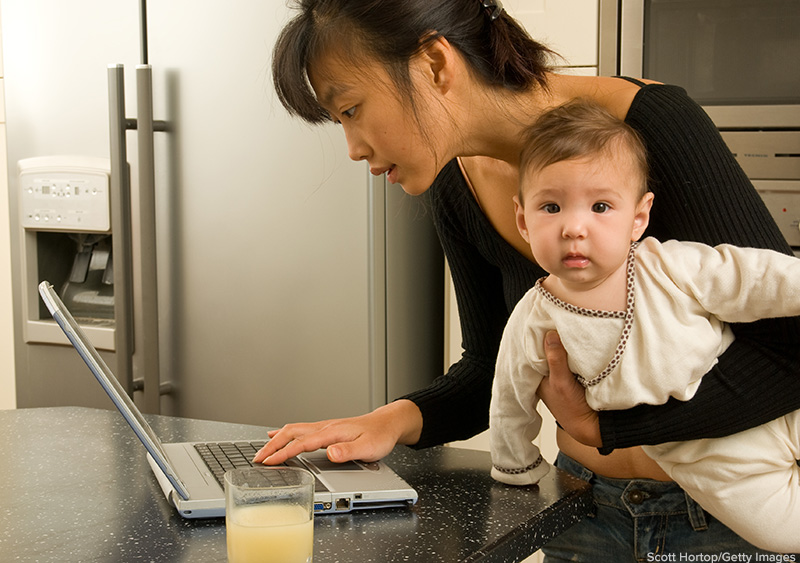 mother working on computer with bored baby. Scott Hortop/Getty Images. MHE Canada;MHE USA