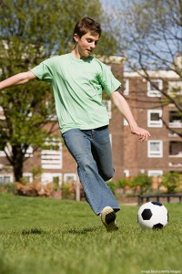 Full-length view of a teenage boy about to kick a soccer ball outdoors.