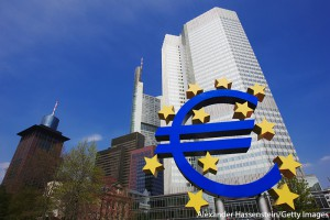 Low-angle view of the Euro sculpture in front of the Eurotower, the European Central Bank headquarters, Frankfurt, Germany.