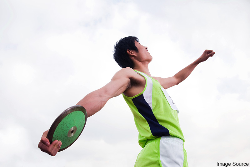 Low-angle waist-length view of a Chinese discus thrower winding up to toss a discus in competition. Image Source. MHE World.