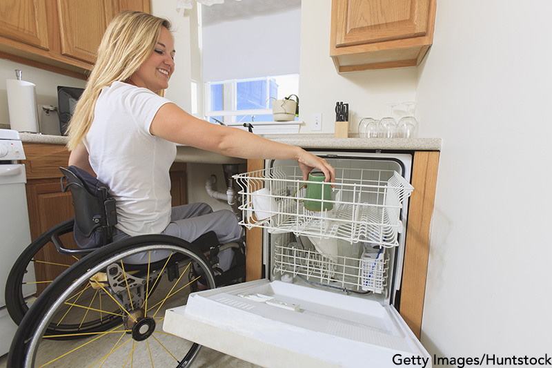Woman with spinal cord injury in her accessible kitchen putting a cup in dishwasher. Getty Images/Huntstock. MHE Canada;MHE USA