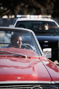 African man in convertible being pulled over by police.