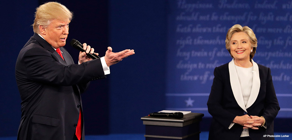 Republican presidential nominee Donald Trump speaks with Democratic presidential nominee Hillary Clinton during the second presidential debate at Washington University in St. Louis, Sunday, Oct. 9, 2016.