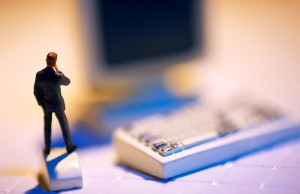 Miniature male figure standing on computer mouse.