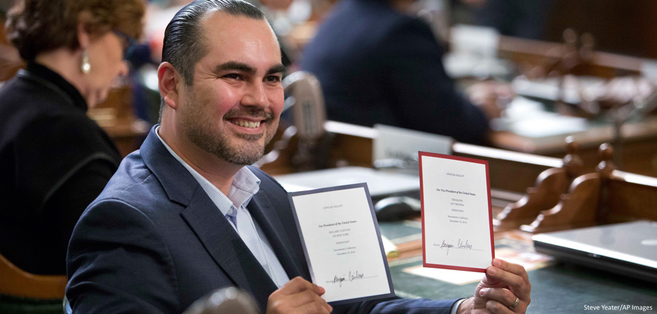 California Electoral College member Benjamin Cardenas displays his ballots to television cameras after casting his votes for president and vice president at the Capitol in Sacramento on  December 19, 2016. (Credit: AP Photo/Steve Yeater)