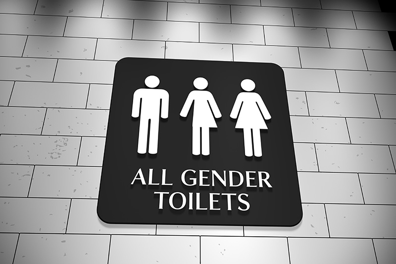 Low-angle view of a sign on a wall for 'All Gender Toilets with symbols for men, trans and women. LGBT issue. Credit: mrtom-uk/Getty Images