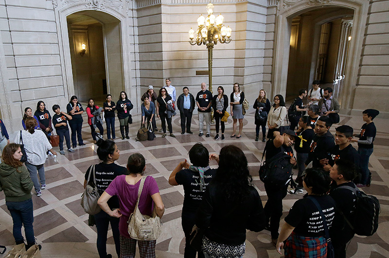 A group calling for San Francisco to maintain its strict sanctuary protections for people who are in the country illegally gathers before a Board of Supervisors meeting at City Hall in San Francisco, Tuesday, May 24, 2016. Credit: Jeff Chiu/AP Images