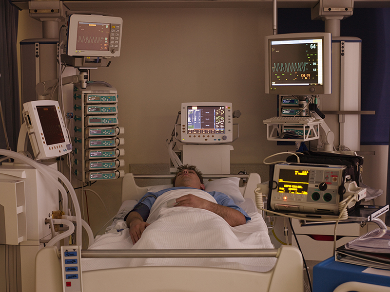 Full-length view of a male patient lying on his back in a dimly-lit intensive care unit. Credit: © Martin Barraud / age fotostock