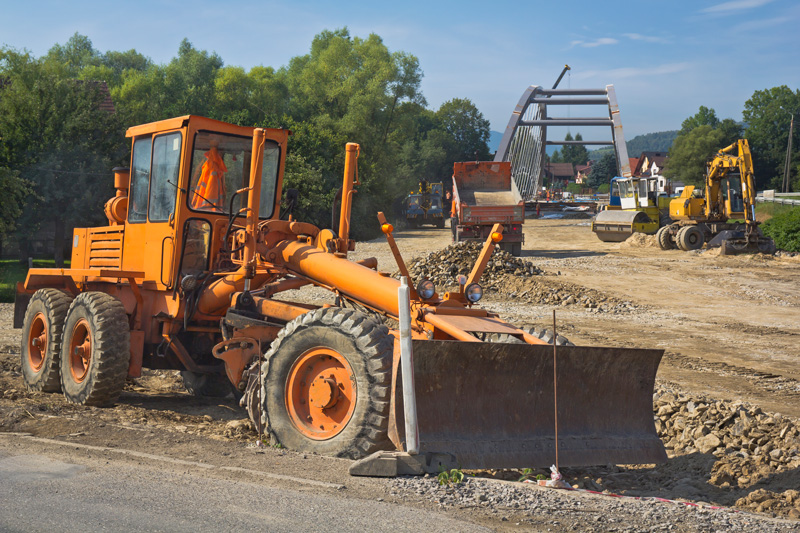 Semi-angled side view of a grader working on a new highway construction in summertime