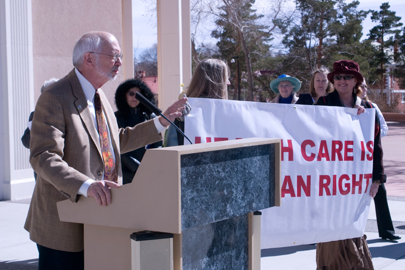 Three-quarter length view of New Mexico State Senator, Jerry Ortiz y Pino, speaking at at an outdoor rally in support of Senate Joint Resolution #5 (SJR5) with women holding a banner to his left.