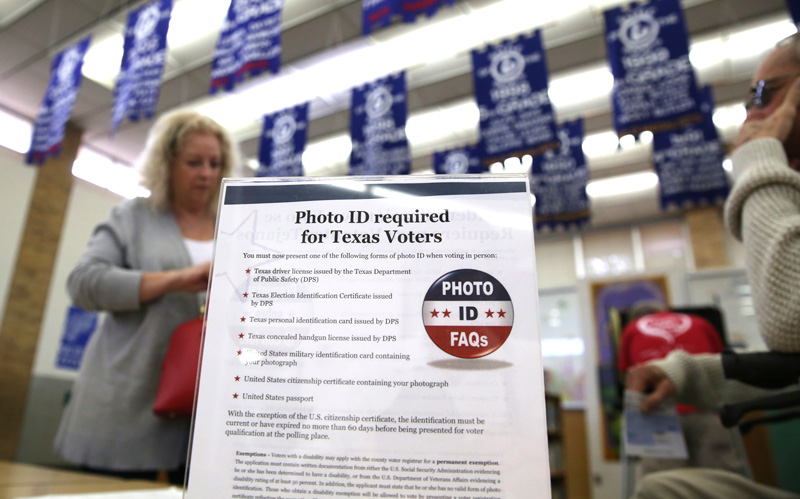 A sign explains voter ID requirements before participating in a primary election in Arlington, Texas.