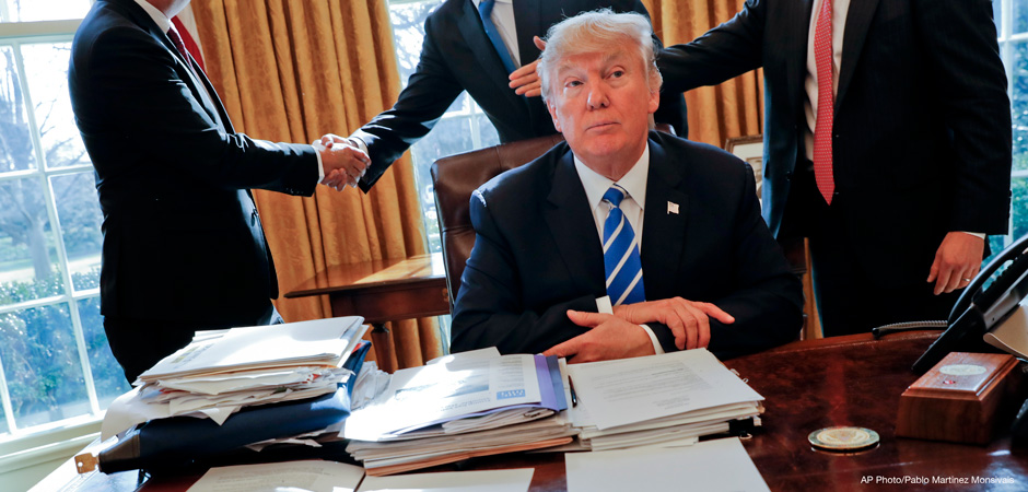 President Donald Trump sits at his desk after a meeting