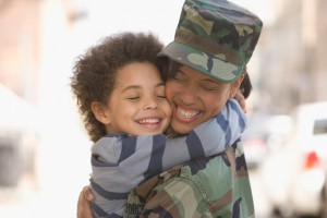 Head and shoulders selective focus view of a happy young mixed race woman, wearing in army fatigues, hugging her 4-5 year old son after returning home, West New York, NJ, USA