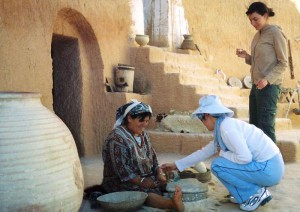 First Lt. Dan Liu helps a Tunisian woman make flour in her home on the outskirts of the Sahara Desert as Capt. Laurie Wax watches during the officers recent four-week Language and Area Studies Immersion trip