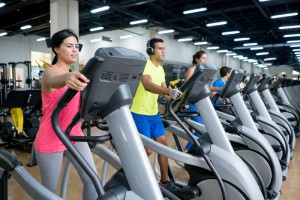 Athletic group of Latin American people at the gym exercising on ellipiticals